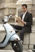 Businessman Sitting By Scooter Reading Newspaper Stock Photos