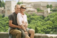 Happy Tourist Couple Posing On Wall - stock photo