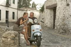 Couple With Scooter Reading Map In Granada Stock Photos