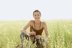Woman Crouching In Field Of Grass Stock Photos