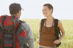 Stock Photo of Hikers With Backpacks Standing In Field