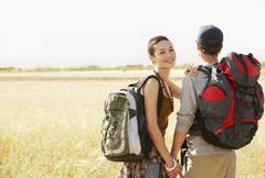 Hiking Couple Holding Hands In Field - stock photo
