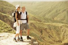 Hiking Couple Standing On Top Of Mountain - stock photo