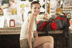 Stock Photo of Female Hiker With Backpack Sitting In Bar