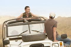Couple In Four-Wheel-Drive Car In Desert - stock photo