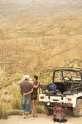 Couple By Car Looking At Desert From Cliff Stock Photos