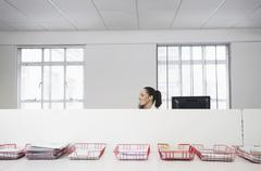 Stock Photo of Businesswoman Using Telephone With Trays Of Documents On Table