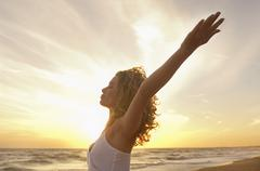 Woman With Hands Raised Meditating At Beach Stock Photos