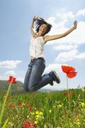 Woman With Arms Raised Jumping In Poppy Field Stock Photos
