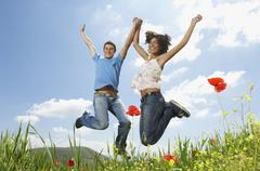 Young Multiethnic Couple Jumping In Poppy Field Stock Photos