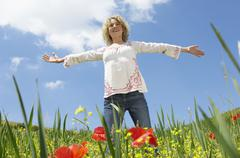 Woman With Arms Outstretched Standing In Poppy Field Stock Photos