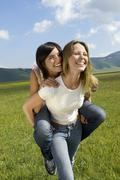 Stock Photo of Woman Giving Piggyback Ride To Friend In Park