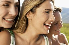 Female Friends Smiling While Looking Away - stock photo