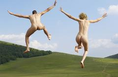 Stock Photo of Naked Couple With Arms Outstretched Jumping In Park