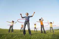 Female Friends Playing With Hula Hoop Against Sky In Park - stock photo