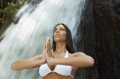 Woman With Hands Clasped Performing Yoga Against Waterfall - stock photo