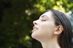 Stock Photo of Woman With Eyes Closed In Park
