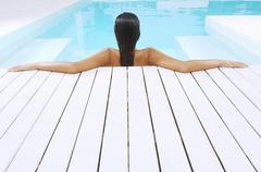 Woman In Swimming Pool Resting On Poolside Stock Photos