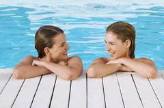 Women Leaning At Poolside - stock photo