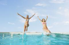 Stock Photo of Excited Female Friends Jumping In Pool