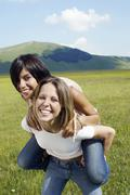 Stock Photo of Woman Piggybacking Female Friend At Park