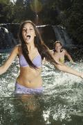 Cheerful Young Woman Playing With Friend In Water - stock photo