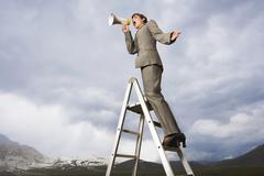 Businesswoman On Ladder Shouting Through Megaphone Stock Photos