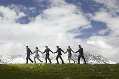 Business People Holding Hands And Walking Through Mountains - stock photo