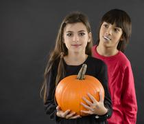 Boy and girl wearing halloween costume with pumpkin on black  background Stock Photos