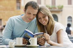 Couple Reading Guidebook At Cafe - stock photo