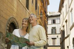 Stock Photo of Couple Holding Map On Street In Rome