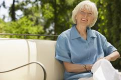 Senior Woman Relaxing On Sofa In Backyard - stock photo
