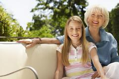 Stock Photo of Grandmother And Granddaughter On Sofa In Back Yard