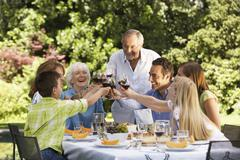 Stock Photo of Family Toasting Wine Glasses At Table In Back Yard