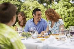 Family Having Lunch At Table In Backyard Stock Photos