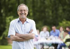 Stock Photo of Happy Senior Man With Family In Background