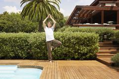 Man Performing Yoga By Swimming Pool Stock Photos