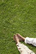 Couple Relaxing On Grass - stock photo