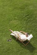 Man Reclining On Lawn In Deck Chair Reading Book - stock photo
