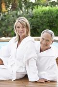 Stock Photo of Happy Couple In Bathrobes Sitting By Pool