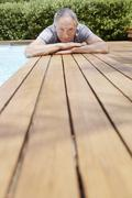 Man Reclining By Poolside Stock Photos