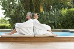 Stock Photo of Couple In Bathrobes Sitting Back To Back By Pool
