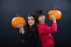 boy and girl wearing halloween costume with pumpkin on black  backgroun - stock photo