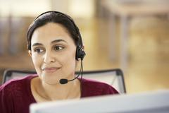 Businesswoman Wearing Headset In Call Center - stock photo
