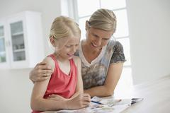 Mother Assisting Daughter In Homework Stock Photos