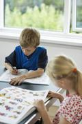 Siblings Studying At Table - stock photo