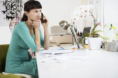 Female Artist Using Cell Phone At Desk Stock Photos