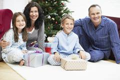 Stock Photo of Happy Family Sitting In Front Of Christmas Tree