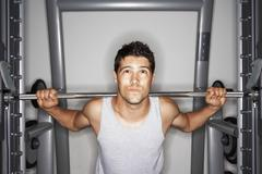 Young Man Struggling To Lift Weights - stock photo