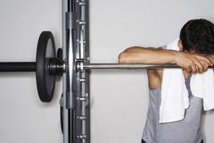 Tired Man Resting On Barbell At Gym Stock Photos
